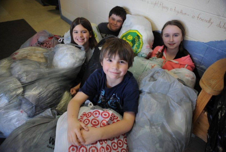 (L-R) Keira Parrill, Ewan Jenkins (front), Rhys Cormier, and Izabelle Jones pose with just a few of the bags created through their efforts (Photo credit: The Western Star)